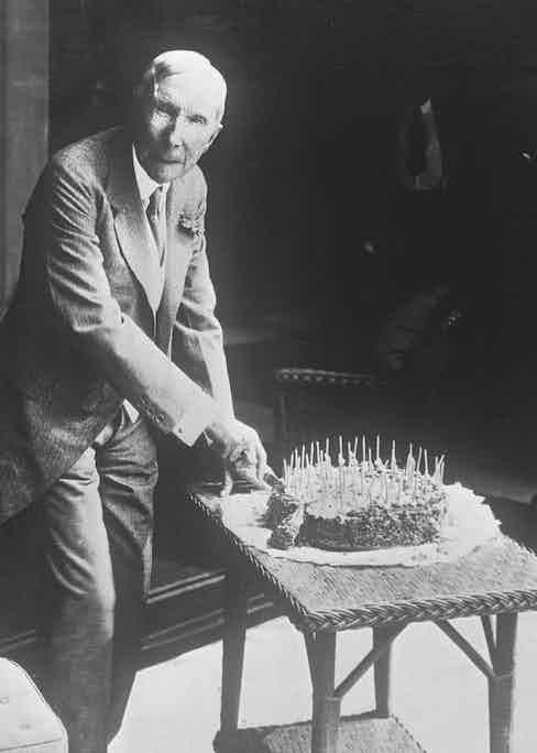 John D. Rockefeller cutting his birthday cake (Photo via Getty)