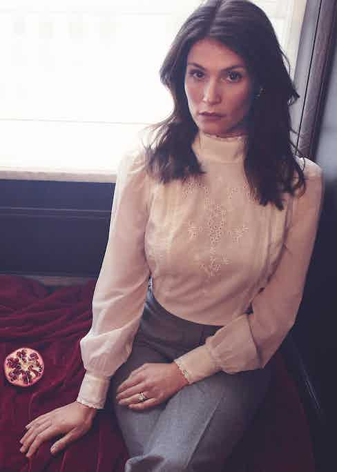 White organic cotton Tennyson open-back broderie anglaise blouse, Reformation; grey flannel high-waisted flare trousers, Caroline Andrew; white-gold 18-carat and diamond droplet earrings, Meváris. Rings, property of Gemma Arterton