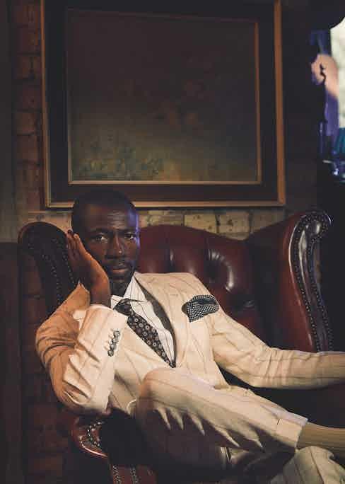 Cream linen, wool and silk chalkstripe suit, Brunello Cucinelli; white cotton striped shirt and brown silk printed tie, both Lardini; grey cashmere pocket-square, Anderson & Sheppard; beige cotton socks, London Sock Company.