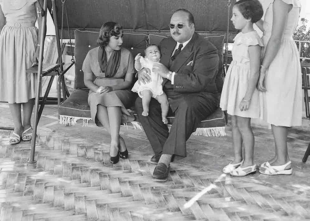 King Farouk on patio with his family.