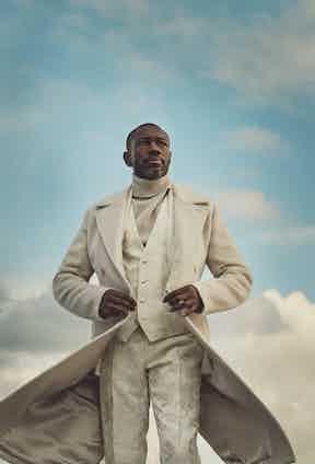 White virgin wool overcoat, white Jacquard trousers and vest, white roll-neck, all Dolce & Gabbana.