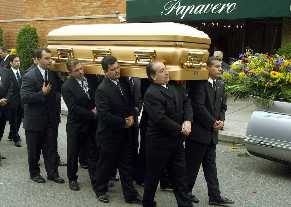 Being carried from his funeral, 2002 (PHOTO/Doug KANTER (Photo credit should read DOUG KANTER/AFP/Getty Images)
