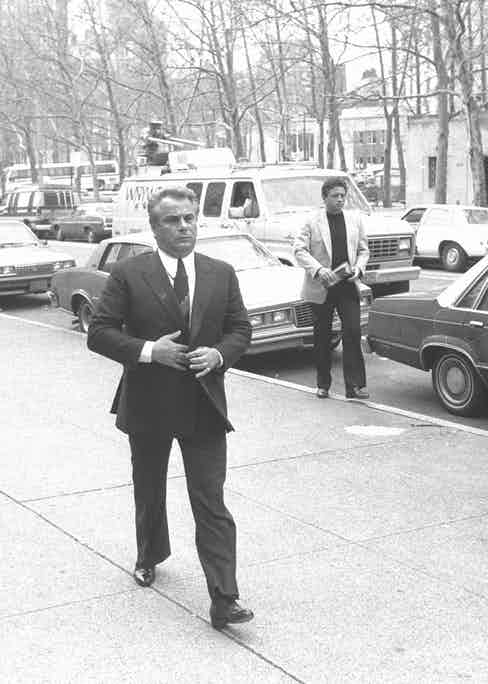 Gotti buttoning his double-breasted suit as he arrives at Brooklyn Federal Court, 1986 (Photo by NY Daily News Archive via Getty Images)