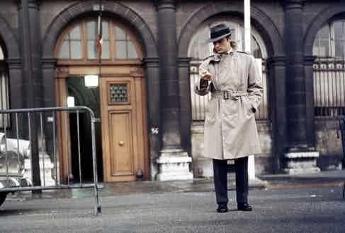 Alain Delon wears a taupe double-breasted trench coat with a belted waist and epaulettes, paired with a grey single-breasted suit and fedora hat in Le Samourai, 1967.