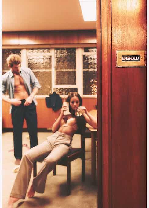 Arielle: Pink Silk bra, La Perla; Grey wool wide-leg trousers, Caroline Andrew. Jacey: Navy flannel suit, Blue denim button down collar shirt, Edward Sexton at The Rake.