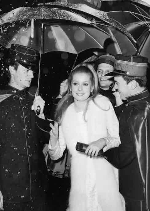 Catherine Deneuve holding colorful umbrellas to shield her from rain falling from a mechanical device as she arrives at the American premiere of director Jacques Demy's film, 'The Umbrellas of Cherbourg,' held at the Little Carnegie Theater, 57th Street, Manhattan, New York City. (Photo by Hulton Archive/Getty Images)