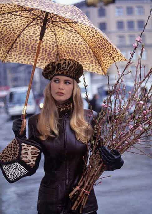 Claudia Schiffer, standing beneath leopard umbrella wearing leather jacket by Louis Dell'Olio for Anne Klein Collection - taken a Union Square Park, Greenmarket in New York City. (Photo by Arthur Elgort/Conde Nast via Getty Images)