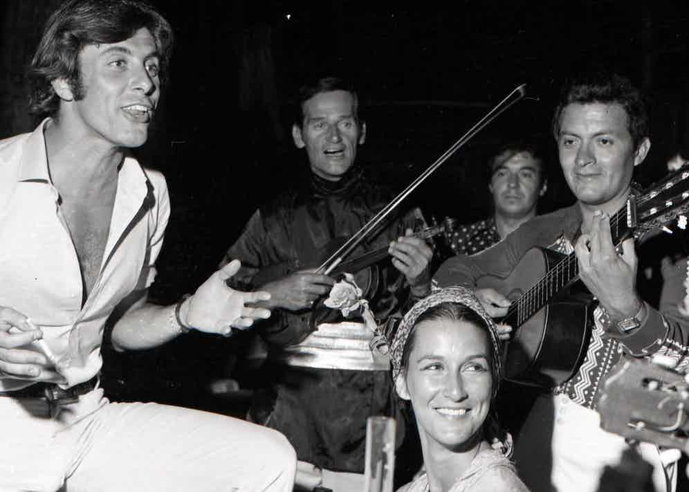 Rizzi, in a signature open-neck shirt, alongside a band of musicians in 1968