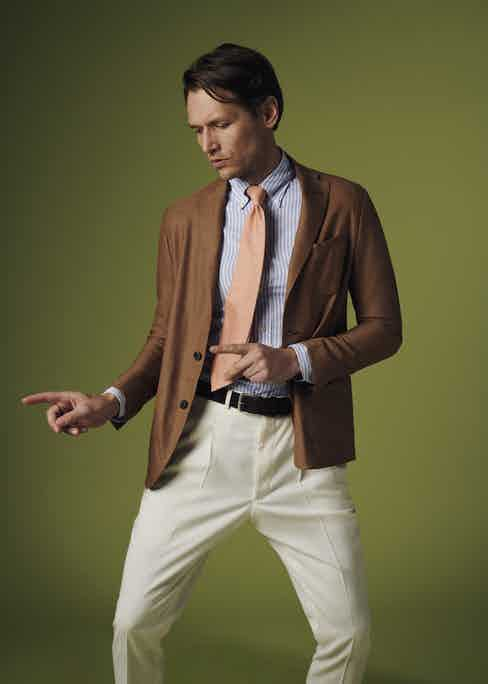 Terracotta wool unlined single-breasted patch pocket jacket, Sacco; light blue striped royal Oxford shirt, Eton; orange silk-linen Ibiza tie with pinstripes, Calabrese 1924; Off white wool gabardine pleated trousers, The Rake Tailored Garments; brown suede belt, Elliot Rhodes.