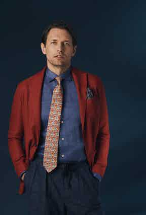Red wool unlined single-breasted patch pocket jacket, Sacco; denim cotton shirt, RTG X Angelo Inglese; yellow silk tie with red and blue floral print, Calabrese 1924; Aleks Dark blue pleated wool mesh drawstring trousers, Kit Blake.