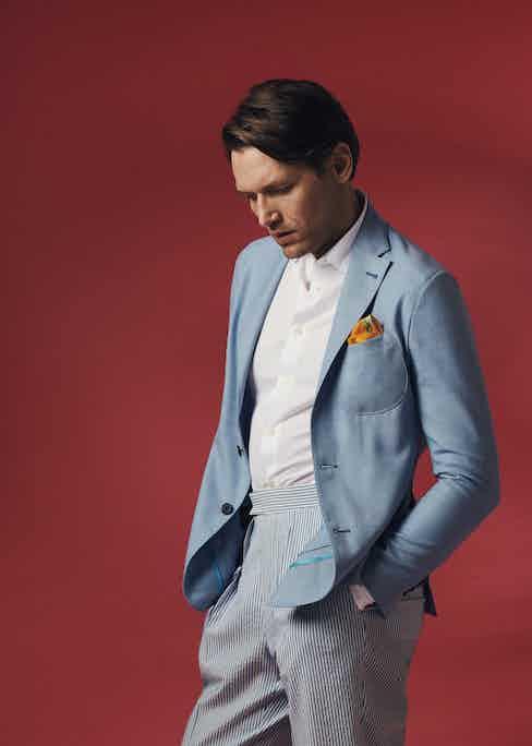 Sky blue unlined single-breasted patch pocket jacket, Sacco; white cotton polo shirt, Eton; Seersucker wool slim Aleks trouser, Kit Blake; orange silk pocket square; Sera Fine Silk.