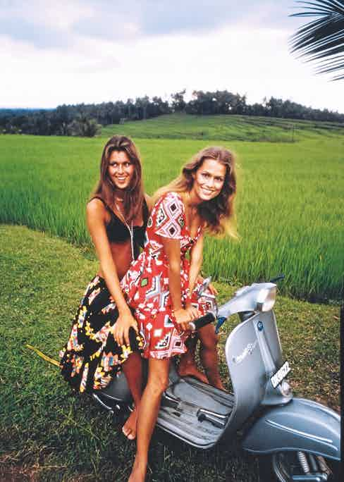 Models Lauren Hutton and Pilar Crespi on a Vespa motor scooter in Bali, wearing outfits by Oscar de la Renta. Lauren Hutton wears a red indian print cotton dress with a laced peplum bodice and a long flounced skirt. Pilar Crespi wears a black nylon bikini top with a long indian print wrap skirt. Choker and necklace by Trifari. Bracelet by Thomas Robbins for Tortolani-Crislu. Hair by Christophe Carita.  (Photo by Arnaud de Rosnay/Conde Nast via Getty Images)