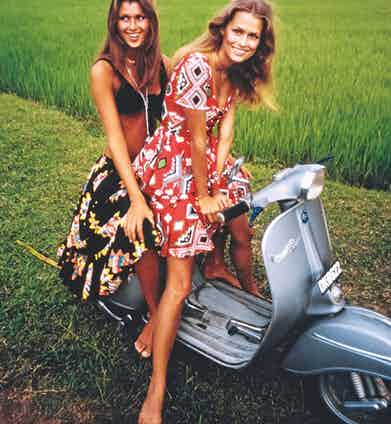 Models Lauren Hutton and Pilar Crespi on a Vespa motor scooter in Bali, wearing outfits by Oscar de la Renta, 1970 (Photo by Arnaud de Rosnay/Conde Nast via Getty Images)