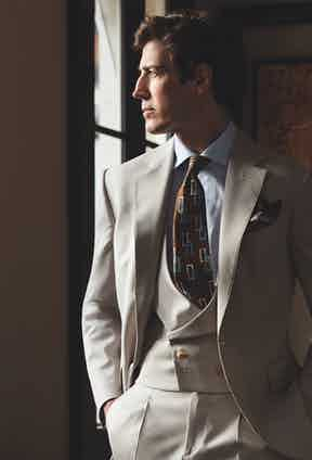 Iconic II: Three-piece beige wool suit; light blue classic shirt; brown silk tie with blue and white rectangles; khaki floral pocket-square.