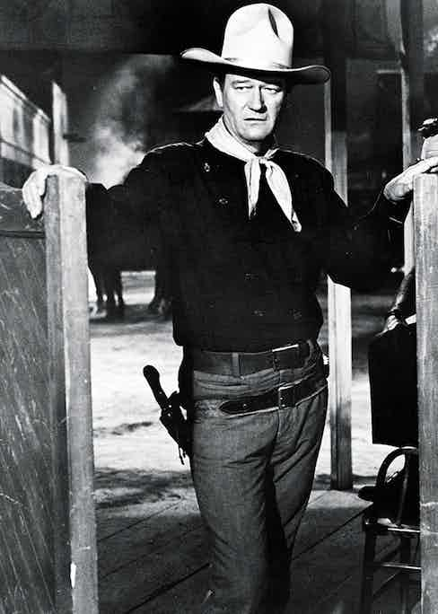 American actor John Wayne (1907 - 1979) wears a Western outfit which includes a pistol in a holster and stands in a doorway in a still from the Cowboy film 'The Man Who Shot Liberty Valance' directed by John Ford, 1962. (Photo by Paramount Pictures/Courtesy of Getty Images)