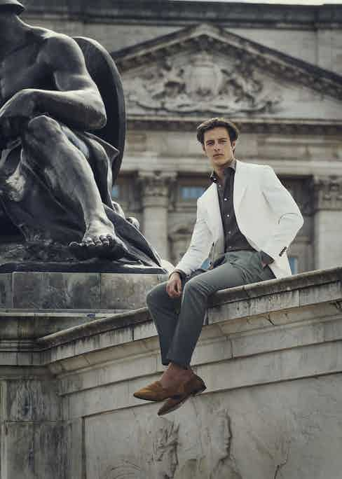 Off-white gabardine single-breasted jacket, brown linen shirt, dark sage trousers.