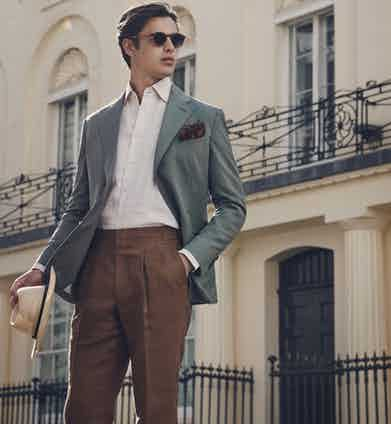 Dark sage single-breasted jacket, beige shirt and tobacco linen trousers.