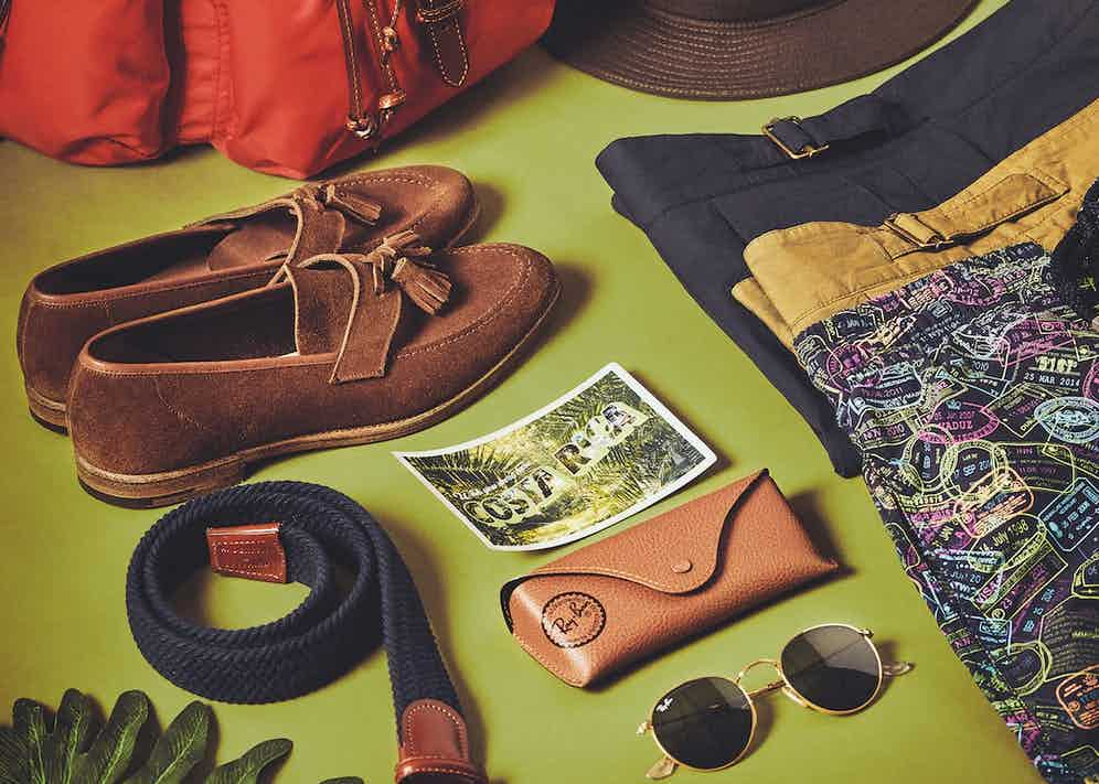 Red leather trimmed nylon backpack, khaki packable cotton trilby and navy cotton elastic woven belt, all Anderson & Sheppard at The Rake; brown snuff suede Solent unlined tassel loafer, Crockett & Jones; military green cotton pleated shorts and navy cotton pleated shorts, both Lardini at The Rake; navy polyamide 'Passport Please!' print 50th anniversary 1980s swimwear shorts, Vilebrequin; round metal gold-and-green lens sunglases, Ray-Ban.