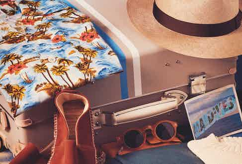 Stone Albion vulcanised fibreboard with leather corners and handles, four-wheel carry-on luggage, Globe-Trotter; azure and pink viscose Kailua Hawaiian shirt, Cordone 1956 at The Rake; rust suede espadrilles, cream wool jumper and light-brown straw Panama hat, all Anderson & Sheppard; seafoam-blue linen pleated stretch Aleks drawstring trousers, Kit Blake at The Rake; bonfire acetate The Birdie sunglasses, E. B. Meyrowitz