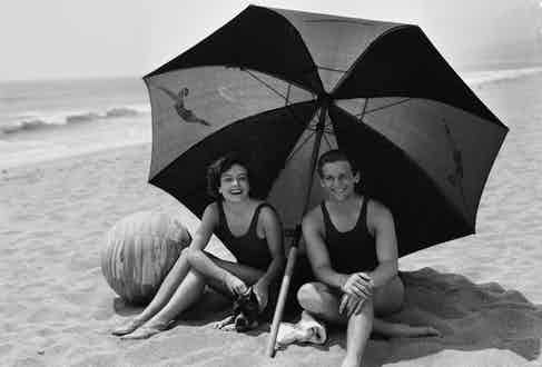 Joan Crawford shares the shade of a large striped beach umbrella with her second husband, actor Douglas Fairbanks Jr (Photo by Clarence Sinclair Bull/John Kobal Foundation/Getty Images)