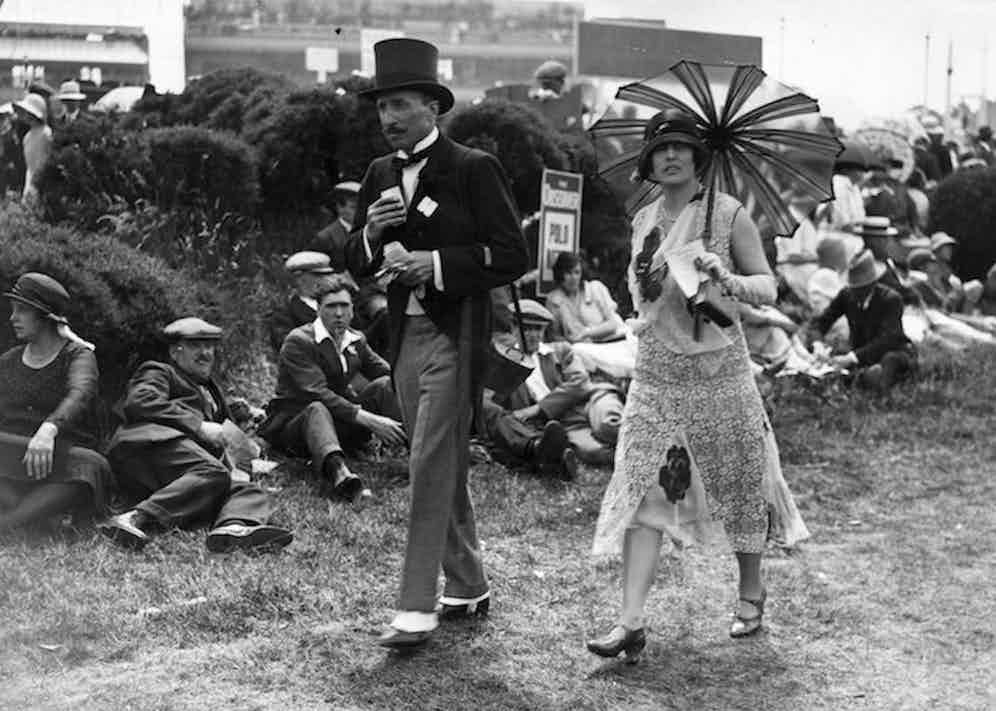 A couple of racegoers at Ascot, the woman in a fashionable dress with a parasol and the man in a morning suit. (Photo by Davis Jr/Topical Press Agency/Getty Images)