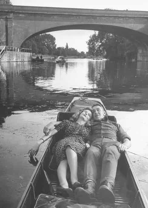 US Sergeant Slim Aarons and an unidentified woman lie in a boat as they float along the Thames River, London, England, 1942. (Photo by David E. Scherman/The LIFE Picture Collection via Getty Images)