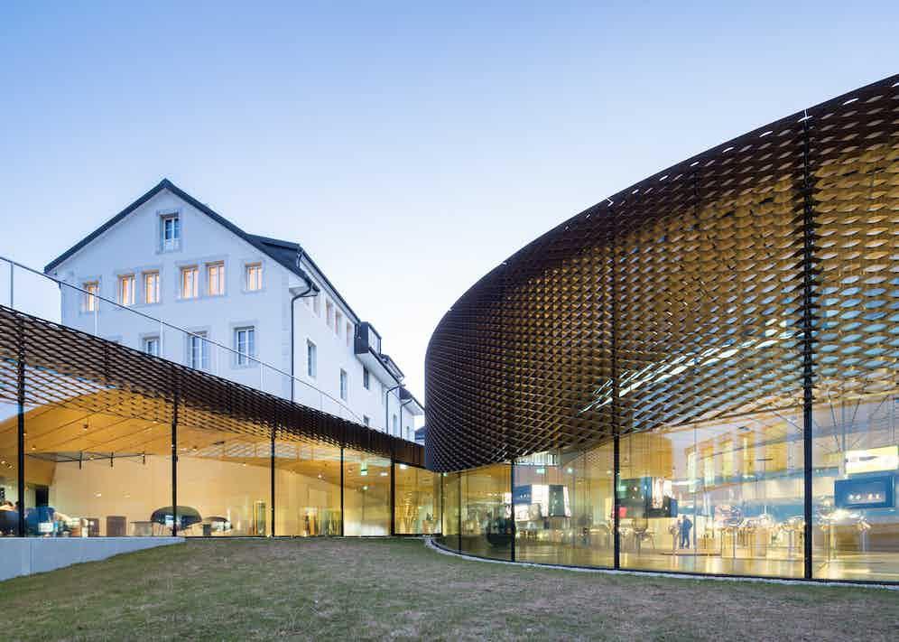 The spiral structure is supported by curved glass walls. A brass mesh runs along the exterior to regulate temperature and light, without obstructing the view.