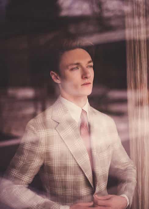 Neutral wool blend check single-breasted Posillipo jacket, De Petrillo at The Rake; cream linen shirt, Anderson & Sheppard; lemonade-pink medallion-print silk tie, Drake's at The Rake. Silver ring, Harrison's own