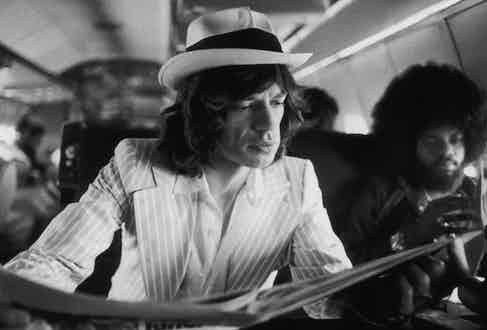 Mick Jagger keeps abreast of current affairs while travelling between concerts in the Rolling Stones' private jet during their 1975 Tour of the Americas. (Photo by Christopher Simon Sykes/Hulton Archive/Getty Images)