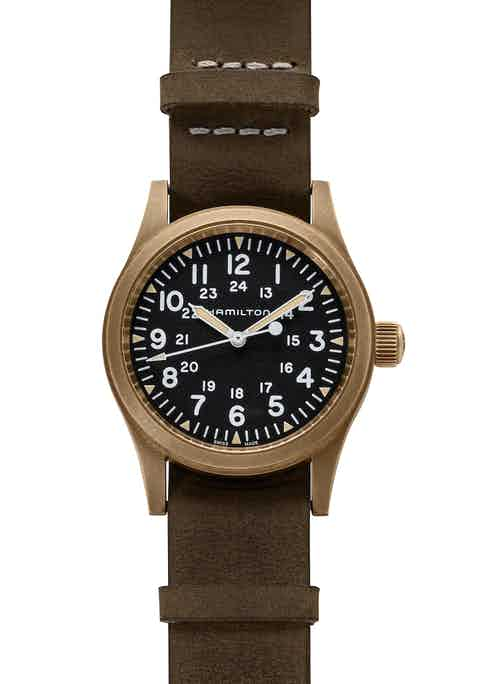 The Khaki Field Mechanical 38mm Bronze has a black dial with luminous triangles on the hour, both 12- and 24-hour time scales, and hash marks for the minutes. (Image: Revolution)