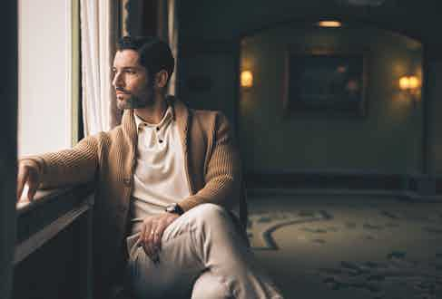 Camel cashmere rib shawl collar cardigan, Anderson & Sheppard; ecru cotton knitted polo, Sunspel; light grey wool trousers, Brunello Cucinelli, Villeret Complete Calendar with blue dial and navy leather strap, Blancpain