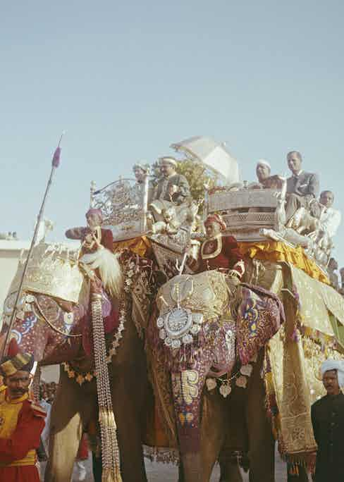 Queen Elizabeth II smiles as she rides in an elaborate howdah alongside Prince Philip (right) on the backs of two ornately decorated elephants through the city of Benares (Varanasi), during her Commonwealth tour of India in February 1961. Sitting beside Prince Philip is Prime Minister of India Jawaharlal Nehru. (Photo by Rolls Press/Popperfoto via Getty Images/Getty Images)