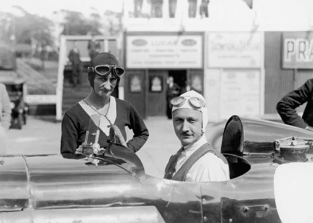Sir Henry Birkin sits in his Blower Bentley and talks with Mrs Elsie Wisdom. (Photo by Barratts/PA Images via Getty Images)